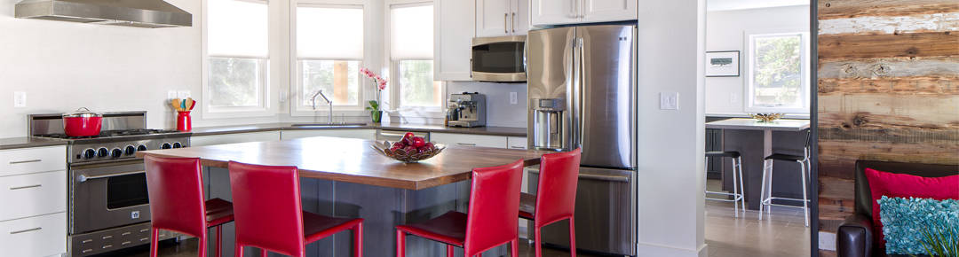 Kitchen with stainless appliances and red chairs